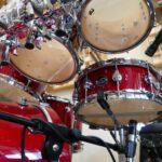 Schlagzeug-Detailfoto unterhalb der Toms mit sichtbarer Snare-Mikrofonierung. Auf diesem Bild sieht man eine Toms und Snare eines Schlagzeugs von unten sowie die Mikrofonierung der Snare-Drum im Tonstudio.