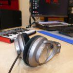 Zu sehen ist der Mixing- und Mastering-Kopfhörer Shure SRH940 am Abhörplatz des Tonstudios. Im Hintergrund befinden sich ein MIDI-Keyboard, ein DAW-Controller und Lautsprecher.