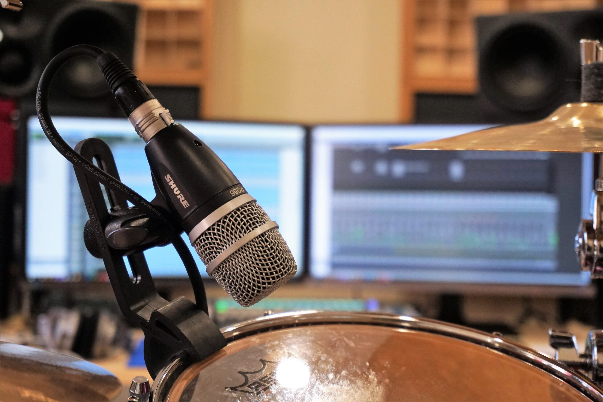 Dynamisches Mikrofon am Rack-Tom (Drumset), PC-Bildschirme und Studio-Monitore im Hintergrund.