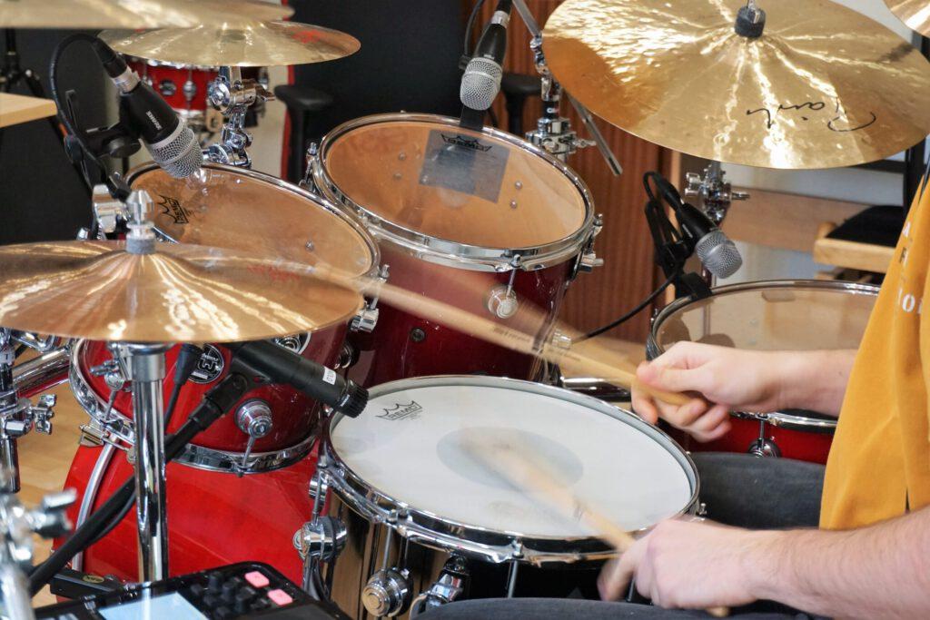 Performance beim Drum Recording. Drummer spielt einen Take im Recording Studio ein.