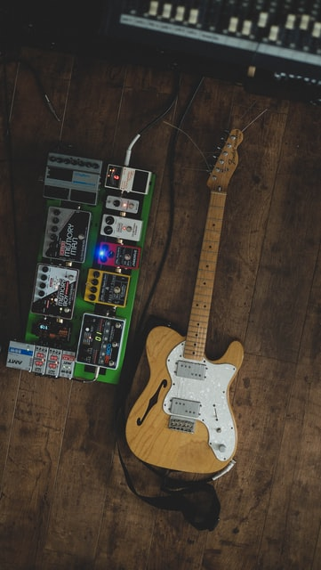 E-Gitarre neben Pedalboard auf Parkettboden im Recording Studio.
