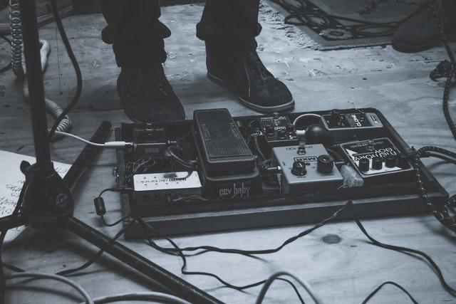 Pedalboard auf dem Boden im Recording Studio, neben Standfüßen eines Mikrofonstativs. Hinter dem Pedalboard sind die Füße des Gitarristen zu sehen, der die Pedale beim Recording bedient.