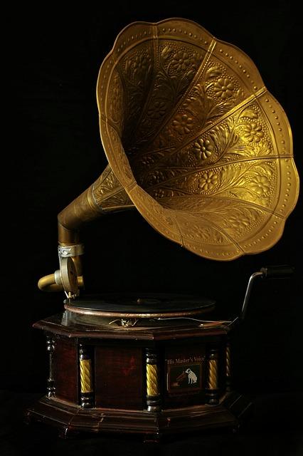 Grammophon mit messingfarbenem Schalltrichter vor schwarzem Hintergrund.