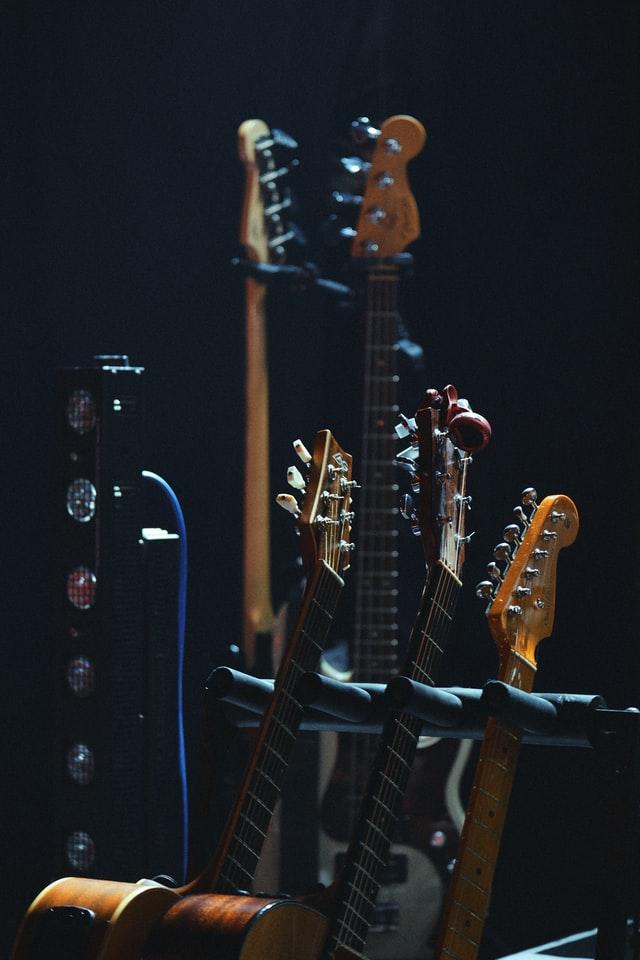 Mehrere fürs Recording Studio geeignete Akustik- und E-Gitarren in einem Gitarrenstativ vor einem dunklen Hintergrund.