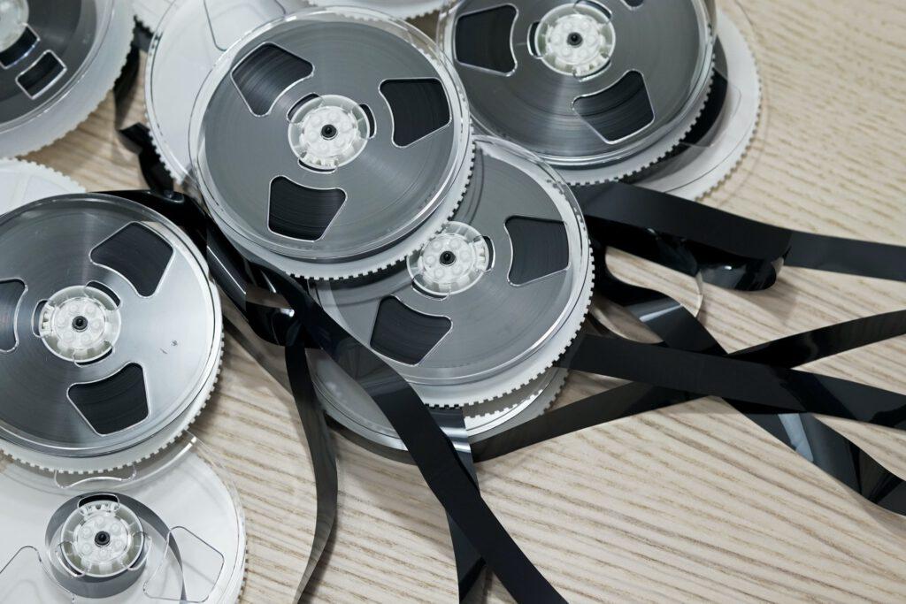 Teilweise abgewickelte Studio-Tonbänder auf einem Tisch. Dank Online Mixing ist die Übergabe von Audiomaterial heute um einiges einfacher.